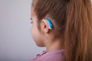 Hearing Aid in Young Girl's Ear. Toddler girl wearing a hearing aid. Studio shot